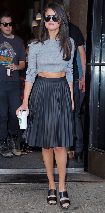 Selena Gomez in a gray knit Topshop crop top with a black leather pleated skirt and black Kurt Geiger mules.