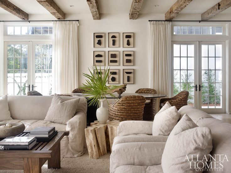 The combination living-and-dining room showcases designer Melanie Turner's deft use of tactile textures to create a serene space. The linen-slipcovered sofas are by Lee Industries, and the coffee table is from South of Market.