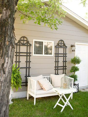 Sun DrenchedThe theme of comfort and contrast continues outside. An outdoor settee with new cushions and pillows sits alongside an X-leg table, creating a small seating area. Trellises frame the seating area, add depth to the white furniture, and turn the side of a garage into a stylish backdrop.