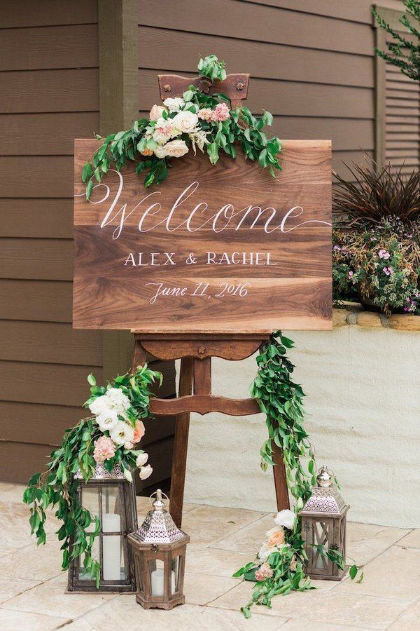 Make the welcome sign the same wooden board that guests sign at the reception. Use the lanterns from table centerpieces too