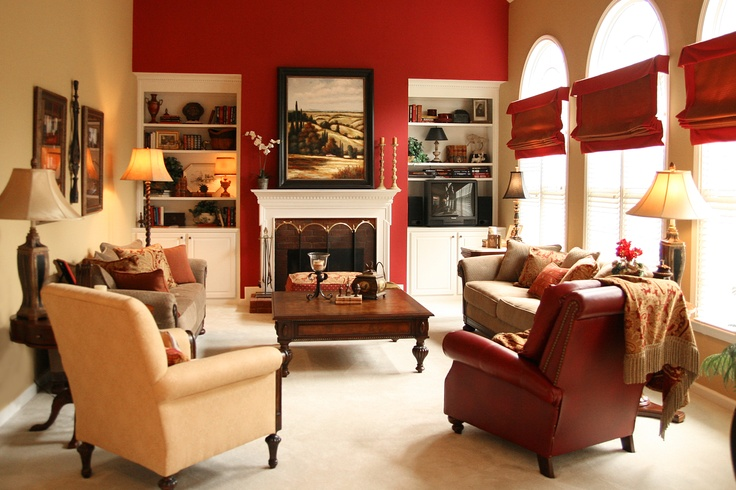 A bold red accent wall draws you into this warm gold family room. Interior Design by Robinson Interiors