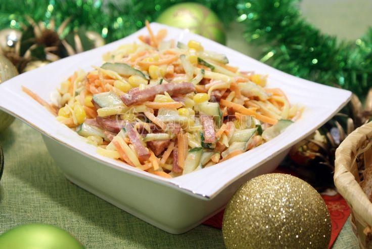 Салат Новогодний серпантин:  Ингредиенты: Консервированная кукуруза — 200 г Свежий огурец — 1 шт Колбаса сервелат — 100 г Сыр твердый — 50 г Морковь по-корейски — 100 г Майонез — 2 ст. л.