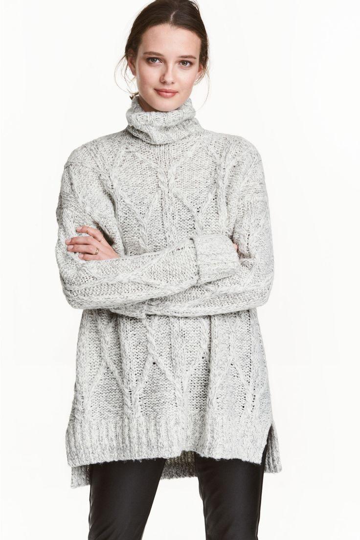Свитер: Длинный, вязаный косами свитер из мягкой пряжи с добавлением шерсти. Заниженное плечо и длинный рукав с пришитым отворотом. Короткие разрезы по бокам.