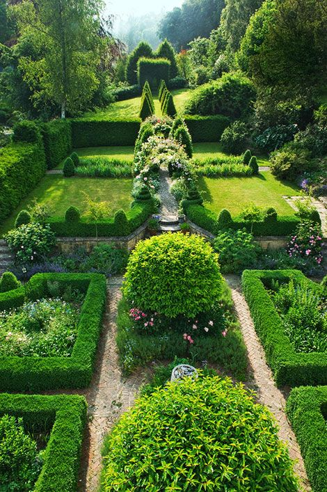 Home owners Amanda and Simon Mehigan, West Dorset, England.  The knot garden behind the house features arches of roses and clematis.