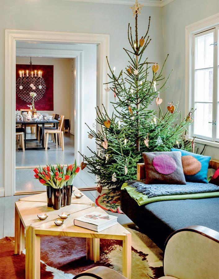 Olohuoneen pikkupöydät ovat hienopuuseppä Petri Koivusipilän ja sveitsiläisen Werner Blaserin yhteistyötä. Sohva on Petrin tekemä ja tyynyt Tiina Tuunasen.  Lapset ovat koristelleet kuusen äidin kanssa itse leipomillaan pipareilla. | PUNAISEN TUVAN JOULU | Koti ja keittiö
