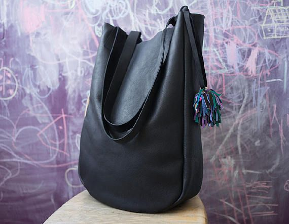 Large, pure and minimalist bag made of high quality black thick leather, matte, soft and solid. On shoulder and arm. The bag does not have a lining, inside is the left side of the skin, suede. With detatch colour leather pompon. Adjusts format A4 without any problem. Dimensions: Height 45 cm (17,7 ) width 32 cm (12,6) depth about 10 cm (4) shoulder straps 67 cm ( 26,5)   For these bag, please expect 5 working days for your item to be made and prepared for shipment!  Standard delivery time…