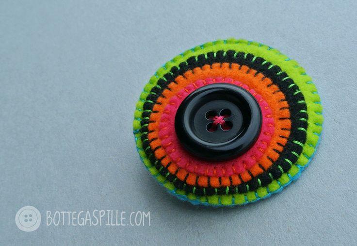 spilla con colori decisi, contrastanti e cerchi concentrici. al centro un bottone nero elegante. tutto dovrebbe concludersi con un bottone così.