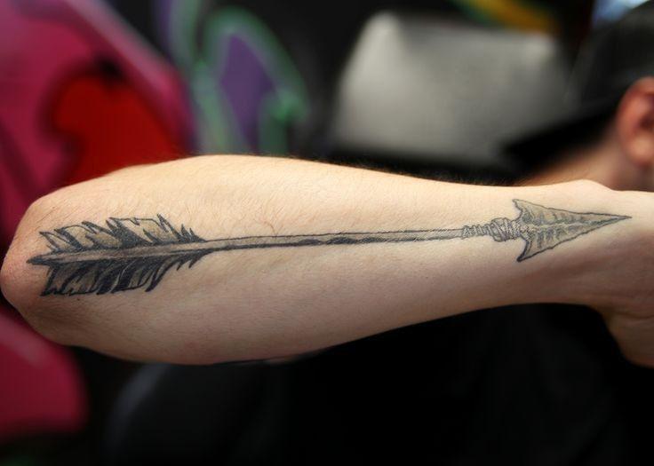Big black arrow tattoo on arm