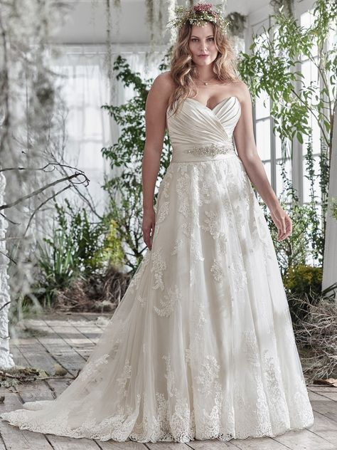 Maggie Sottero - KAMIYA, Timeless and elegant, this romantic lace and tulle A-line plus size wedding dress features a stunning L'Amour satin pleated bodice and lightweight lace and tulle skirt, accented with a delicate Swarovski crystal embellishment at t