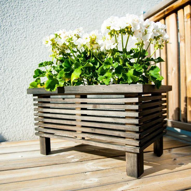Stabil og enkel blomsterkasse i svart tre og med en innvendig del av sink som hever blomsterbedet litt fra bakken.