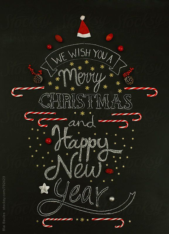 We wish you a merry Christmas and happy new year, written on a chalkboard and composed with Christmas ornaments.