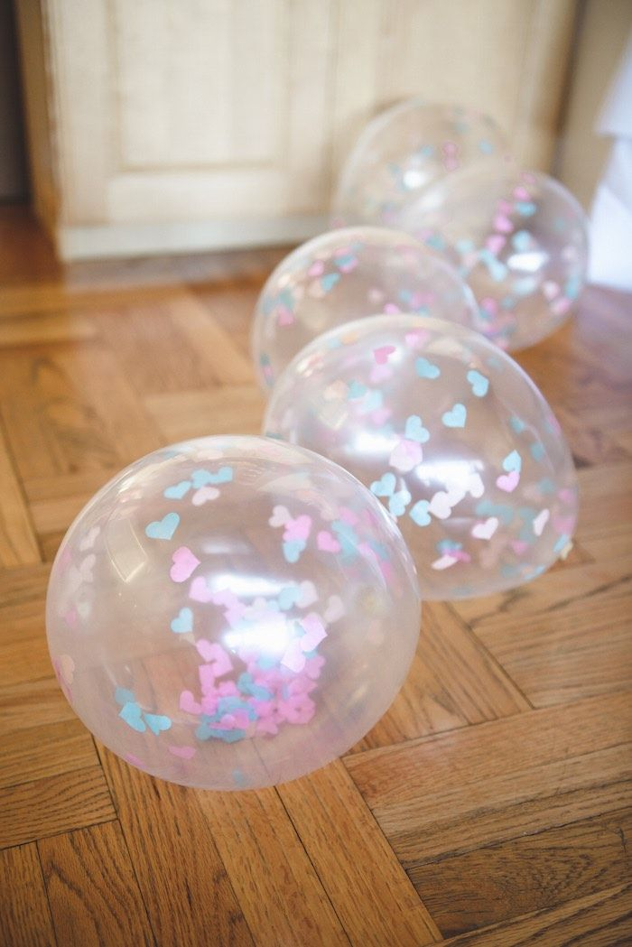 Fill clear balloons with coloured paper cutouts that are perfect for your theme.