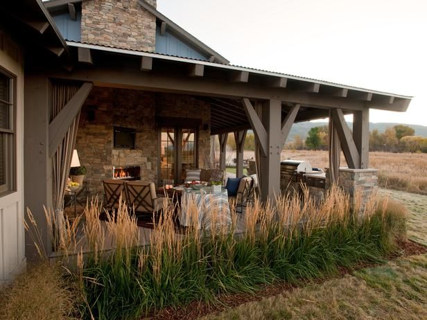 outdoor living room. love the rock, the blue color, the rustic feel and the curtians.