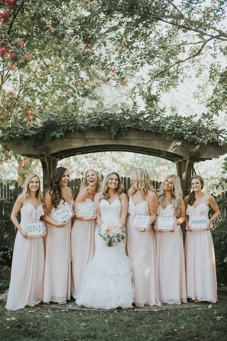 Adorable bridesmaid wedding photo idea with each holding up a sign describing how they met the bride (Feather & North Photography)