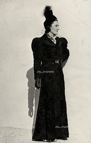 """Model presents an article created by the Italian couture house """"Cicogna"""" consisting of a breitschwanz overcoat gathered at the waist by a belt with jewelled buckle, complemented by a small plumed hat with veil1935 - 1939 (c) Bogino, LuisFratelli Alinari Museum Collections, Florence"""
