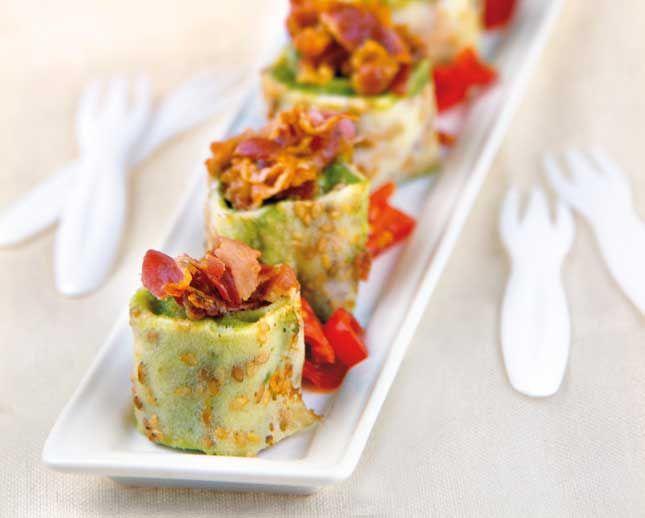 Crêpes con crema di avocado e pancetta. Tagliate a mo' di rotolini, sono dei bocconcini finger food e possono essere serviti per aperitivo o in un buffet.