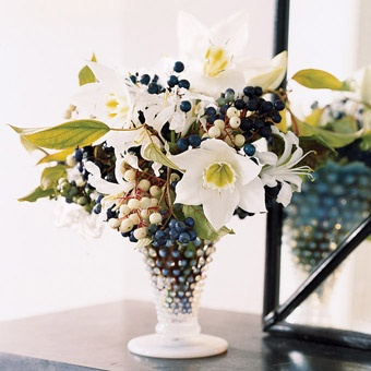 centerpiece from Domino Magazine: dark-blue porcelain vine and creamy dogwood berries, + a few white eucharis in a wide-mouth container that lets stems splay open; photo by Annie Schlechter