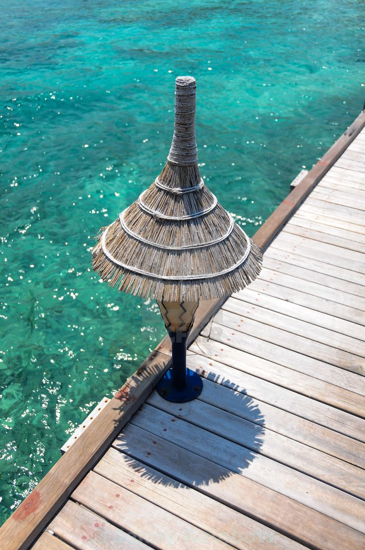 """Lamp on the wooden jetty over blue water"" by Jenny Rainbow - £10"