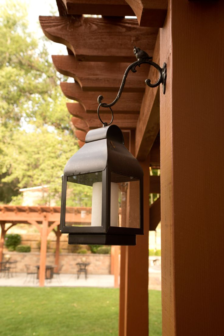 Metal candle lanterns offer romantic lighting at night and give a nice stark contrast against the Rich Sequoia stain on this beautiful solid wood pergola.