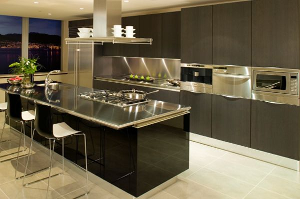 Stainless steel kitchen - A retro-modern kitchen with multiple stainless steel surfaces and black/grey accents. The back wall features cabinetry with built-in appliances, and a sink workspace.