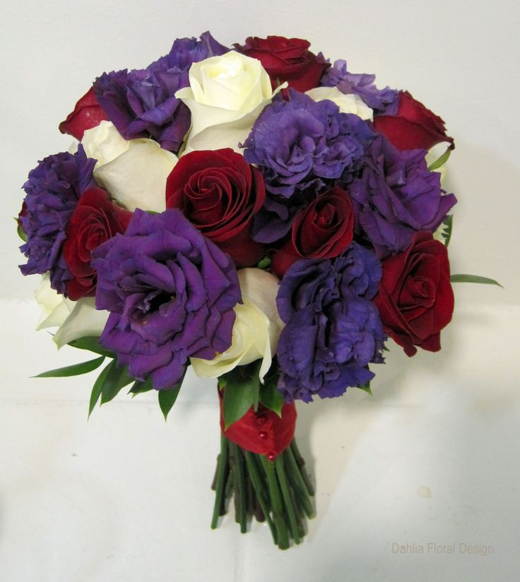 Rich jewel tones of red and purple are accented with ivory in this bridal bouquet featuring roses and lush lisianthus.