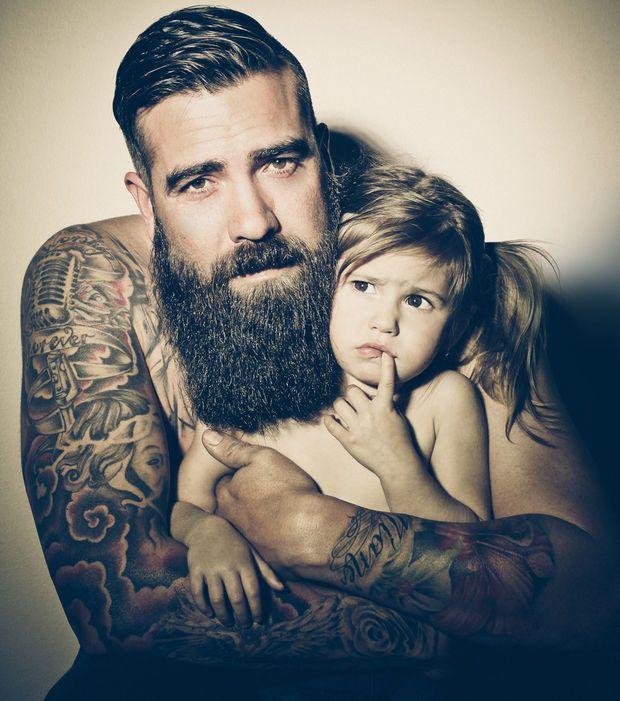 Sublime portrait d'un homme barbu et tatoué avec sa fillette
