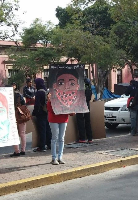 Acción por Ayotzinapan, una estudiante muestra el dibujo en tamaño grande de uno de los estudiantes desaparecidos para que sea visible a los demás durante una manifestación. La estudiante oculta su rostro ya que lo importante en ese momento era mostrar el del estudiante desaparecido. La foto la tome con el celular y esta sin retoques ni edición.