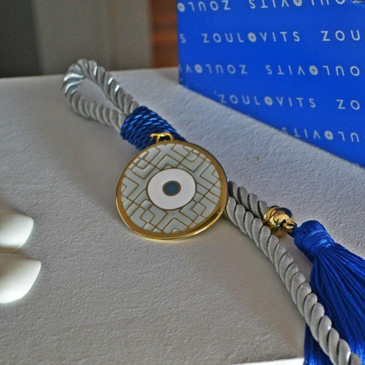 Χειροποίητο γούρι μάτι, επίχρυσο στογγυλό τρίχρωμο: γκρι, χρυσό και μπλε, δεμένο σε γκρι σατέν χοντρό κορδόνι με μπλε φούντα.