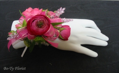 Prom Flowers - Wrist corsage featuring assorted pink flowers accented with pink ribbon and jewels.