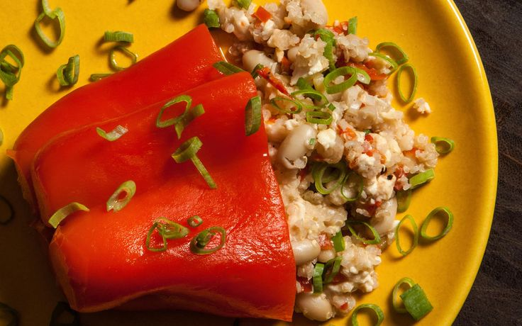 An easy recipe for red bell peppers stuffed with quinoa, feta cheese, and white…