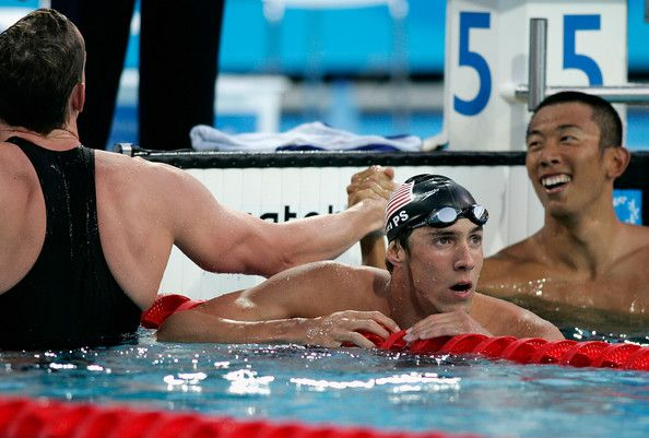 Michael Phelps Photos Photos - Michael Phelps of USA is seen next to Stephen Parry of Great Britain (L) and Takashi Yamamoto of Japan (R) after the men's swimming 200 metre butterfly final on August 17, 2004 during the Athens 2004 Summer Olympic Games at the Main Pool of the Olympic Sports Complex Aquatic Centre in Athens, Greece. - Olympics Day 4 - Swimming