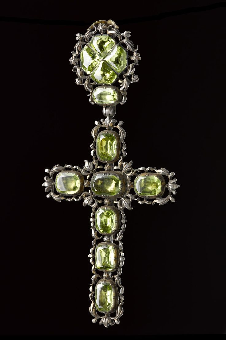 Pendant of silver in the form of a Latin Cross with scrollwork set with light green peridots, with a reliquary containing some looped gold wire and a small label: probably Italian, 18th century