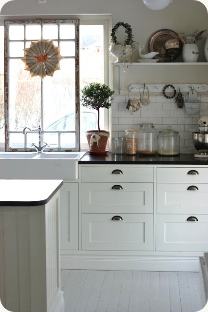 Kitcken - white cabinets, black counters, silver drawer pulls. .. love the farm sink.