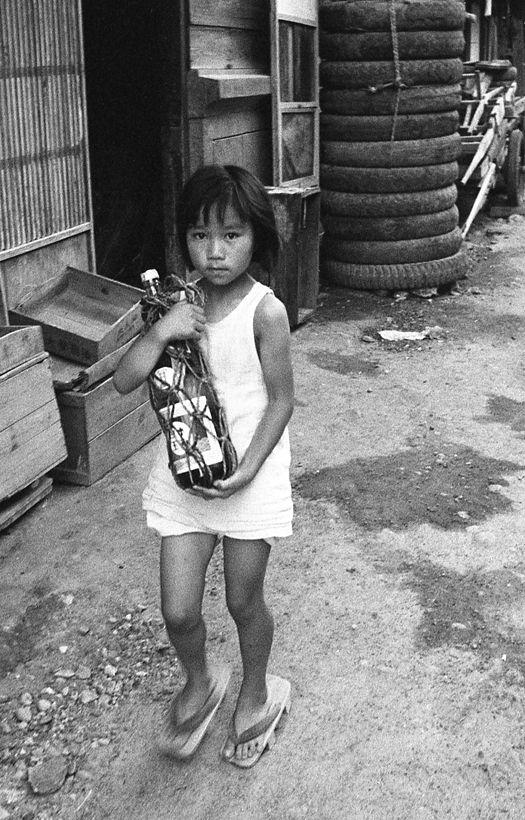 Little girl w a big issho-bin (a 1.8-litre of sake) bottle, Furukawamachi, 1956