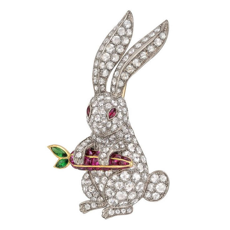 Diamond Rabbit with Ruby Carrot Brooch - Rabbit brooch, the body set with circular-cut diamonds accented by ruby eyes, the rabbit holding a ruby-set carrot with emerald-set leaves, mounted in 18k white gold, the carrot and pin stem in yellow gold.  1950's