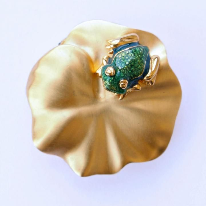 """Estee Lauder solid perfume compacts are always beautifully collectible, and this one for """"Knowing"""" perfume is no exception: a matte goldtone lilypad with a tiny bright green enamel frog perched on it. Compact measures approximately 1-3/8 inch in diamet..."""