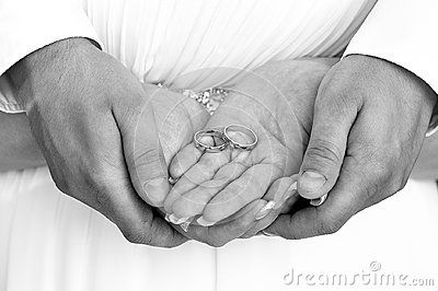 Newlyweds holding wedding rings in hands