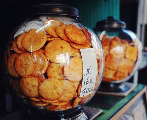 Senbei are a type of Japanese crackers that are made from rice and usually coated with soy sauce or salt. They are often eaten with green tea as a casual snack and offered to visiting house guests as a courtesy refreshment. It is said that the original type of senbei came from China around 200 B.C., and the current Japanese senbei first appeared at Soka, a city in Saitama prefecture.