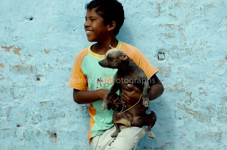 A boy holds his dog against a colorful backdrop in Pisco, Peru, South America. Gary Moore photo. #photojournalism #peru #realworldphotographs #southamerica #photojournalist #kelowna #dog #boy