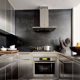 A folk-art rooster from the 1800s overlooks a modern New York City kitchen designed by Robert Passal. The cabinets are made of stainless steel, and the space is equipped with a Miele oven, cooktop, and hood.