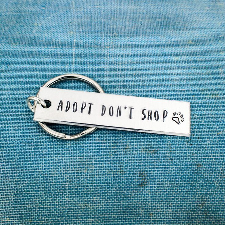"This ""Adopt Don't Shop"" aluminum keychain is stamped, one letter at a time, on a 1/2"" x 2"" aluminum blank and assembled by hand. There is a little paw print at the end of the phrase. The rectangles ar"