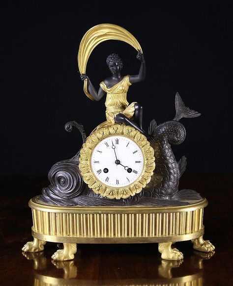 A Fine Quality French Empire Bronze & Gilt Bronze Mantel Clock. The white enamel dial in a gilt drum case set into the back of a dark patinated scrolling dolphin and surmounted by the seated figure of a black girl dressed in gilt tunic waving a scarf above her head. The nulled oval gilded plinth raised on six lion paw feet, 15 ins (38 cms) high, 12 ins (31 cms) wide.