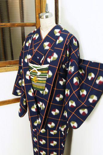 ミッドナイトネイビーに、赤白黄色で色分けされた水玉で飾られた大胆な格子模様が織り出された羽織と着物のセットです。