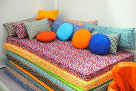 """Stack of multiple fabric-covered foam pads.  makes a cushy """"sofa"""" in the playroom, and can be pulled apart for multiple sleepover guests, movie night pillows, or tumbling games, etc."""