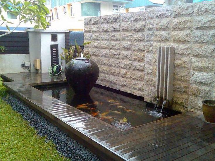 carpes koï dans le petit bassin moderne dans l'arrière-cour avec fontaine et cascade