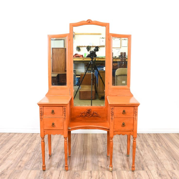 This vanity is featured in a solid wood with a distressed orange finish. This cottage chic style vanity dresser has a tri-fold mirror, 4 spacious drawers, floral motifs and dovetailed joinery. Perfect for any girl's room! #cottagechic #dressers #vanitydresser #sandiegovintage #vintagefurniture