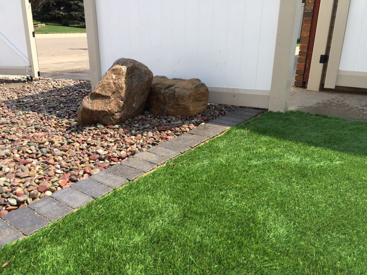 Installed boulders set in rainbow rock. The turf is bordered by Barkman paving stones