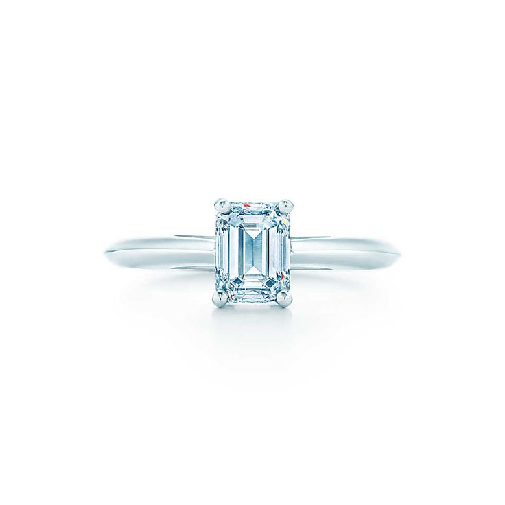Set in platinum, a classic emerald-cut diamond creates a dramatic presentation.