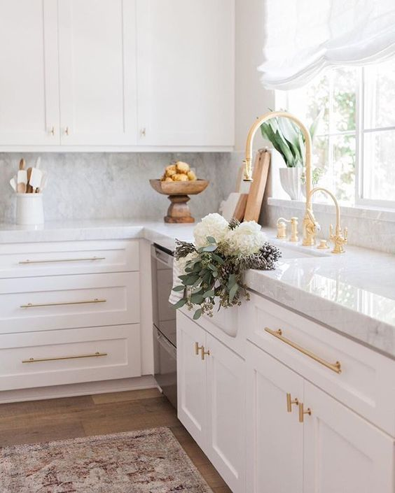 Beautiful white kitchen: hardwood floors, white cabinetry with gold chromeware and marbled counter tops.