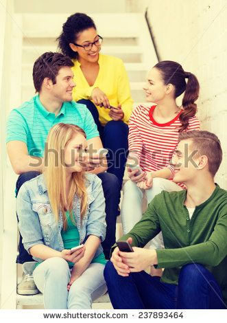 education, school and technology concept - smiling students with smartphone having discussion at school